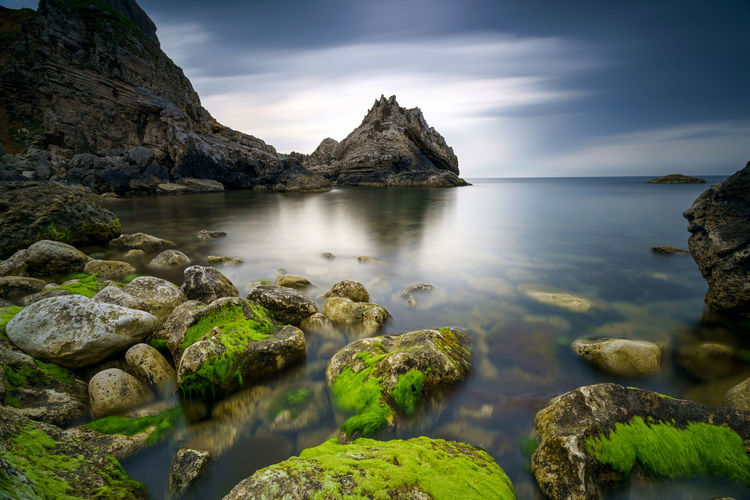 Scenic view of rock formation in water against sky