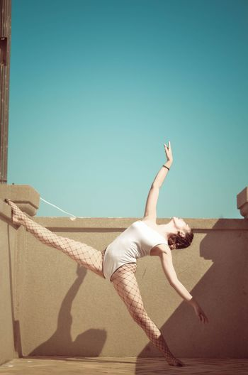 Ballet dancer dancing on building terrace against clear blue sky during sunny day