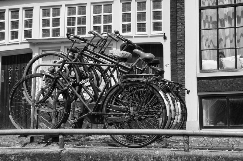 Amsterdam Architecture Bicycle Bicycle Rack Building Exterior Built Structure Day Land Vehicle Mode Of Transport No People Outdoors Parking Spoke Stationary Tire Transportation Wheel Window
