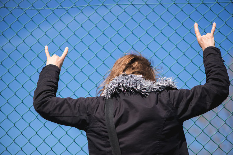Woman and fence Adult Arms Raised Back Backgrounds Blue Blue Sky Conceptual Day Fence Human Body Part Humanback Leisure Activity Lifestyles Metal Fence One Person Outdoors People Prison Protest Real People Rear View Sky Standing Woman Women
