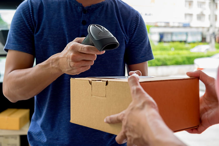 Midsection of delivery man scanning parcel held by customer