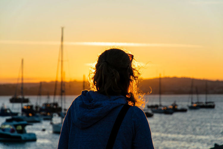 Rear view of woman against sea and sky during sunset
