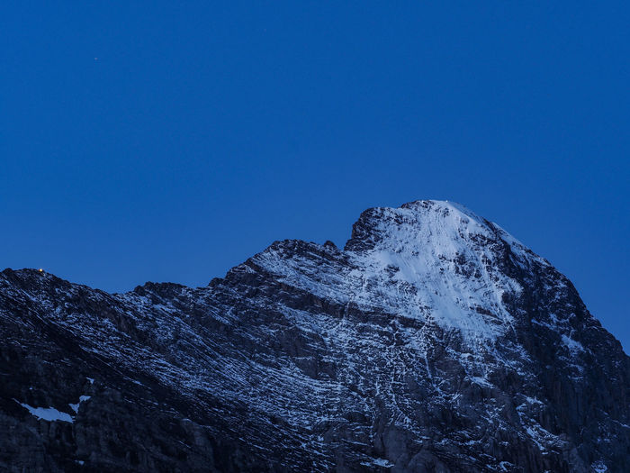 Low angle view of snowcapped mountains against clear sky at blue hour