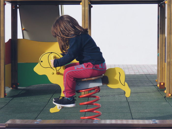 Side view of girl sitting on play equipment
