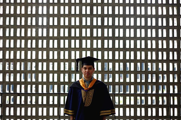 Portrait Of Man In Graduation Gown Standing Against Window