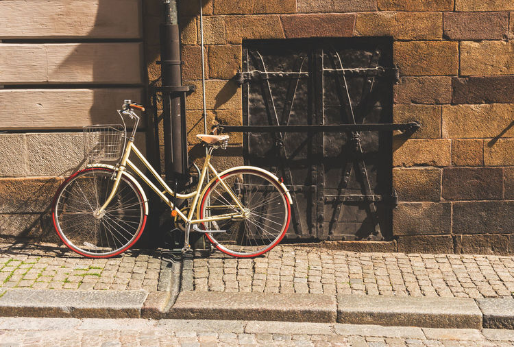 Bicycle parked against brick wall
