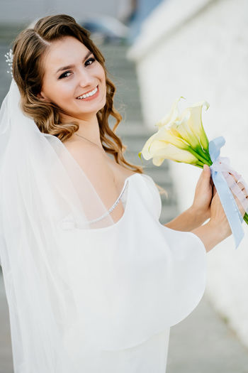 Portrait of smiling young woman holding white rose