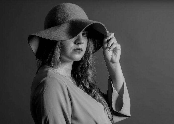 Portrait of woman wearing hat against gray background