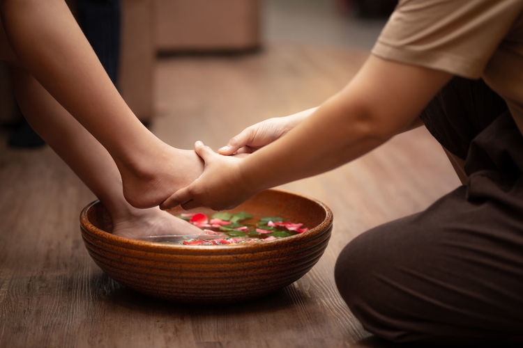 Woman feet dipped in water with petals in a wooden bowl.