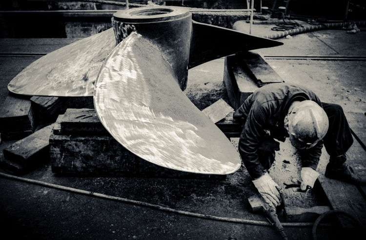 Prop repair Black And White Day Dirty Dry Dock Industry Outdoors Propellor Ship Shipbuilding Shipbuilding Yard Stationary Work Worker