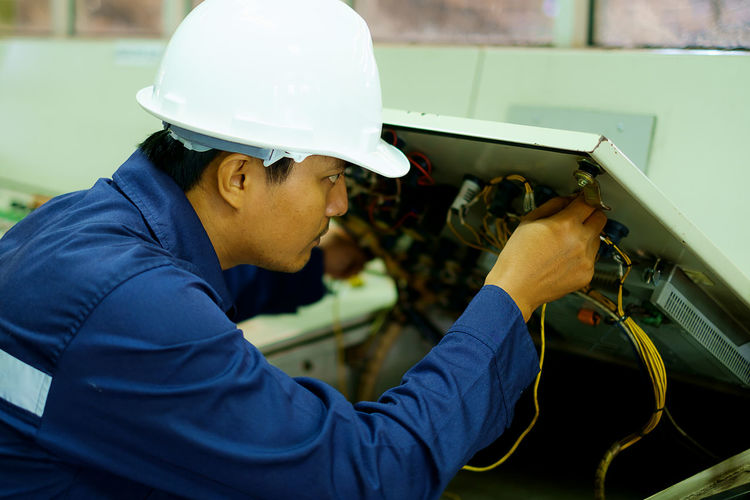 Concentration Electrician  Engineer Expertise Hardhat  Headwear Helmet Holding Indoors  Industry Maintenance Man Manual Worker Manufacturing Occupation Occupation Occupational Safety And Health One Person Protective Workwear Real People Safety Side View Skill  Technology Working Young Adult