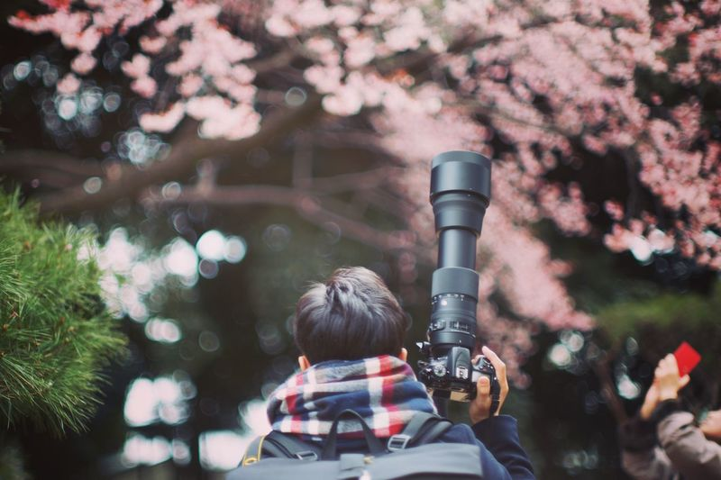 Close-up of man holding camera against trees