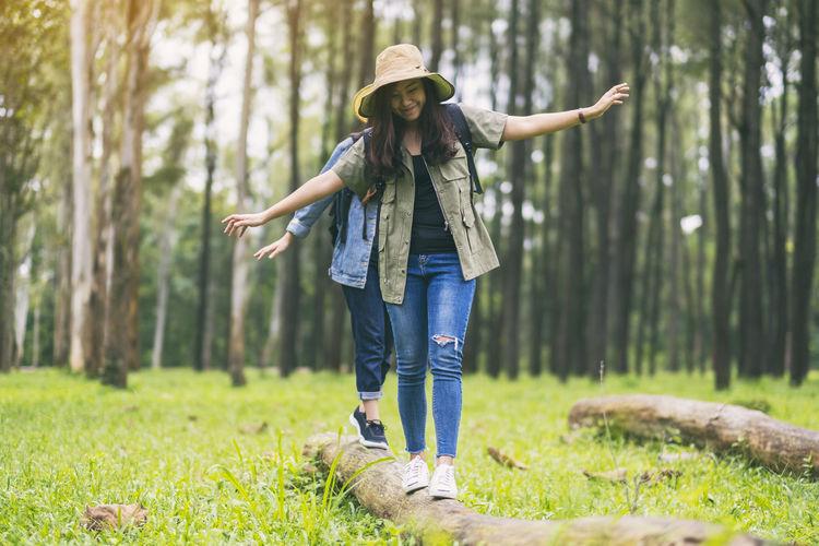 Friends walking on log in forest