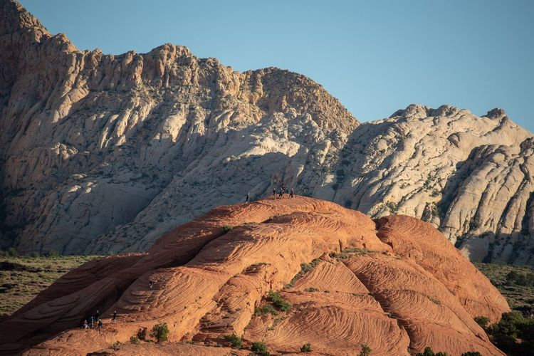 Landscape of people on rock formation, white hills in the back in snow canyon state park in utah