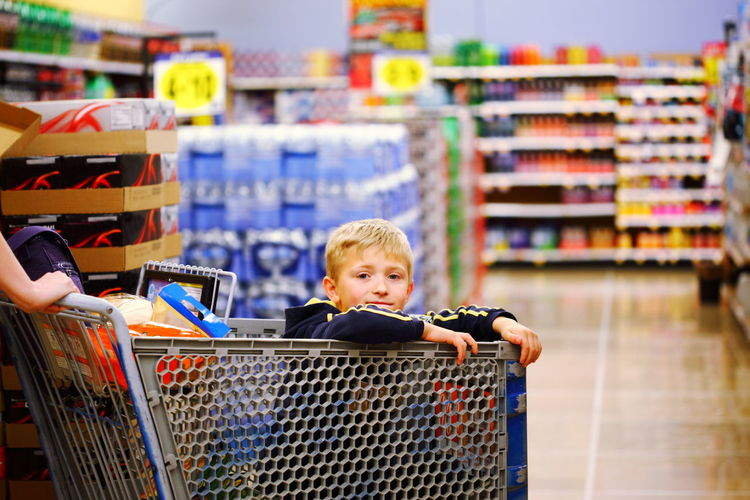 Portrait of boy sitting in shopping cart at store