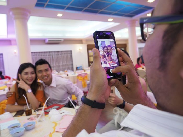 Photographer use smart phone to capture a photo of a couples in party. EyeEm Selects Wireless Technology Technology Smart Phone Mobile Phone Portable Information Device Photography Themes Photographing Group Of People Communication Camera Togetherness Women Holding Happiness Adult Portrait Friendship