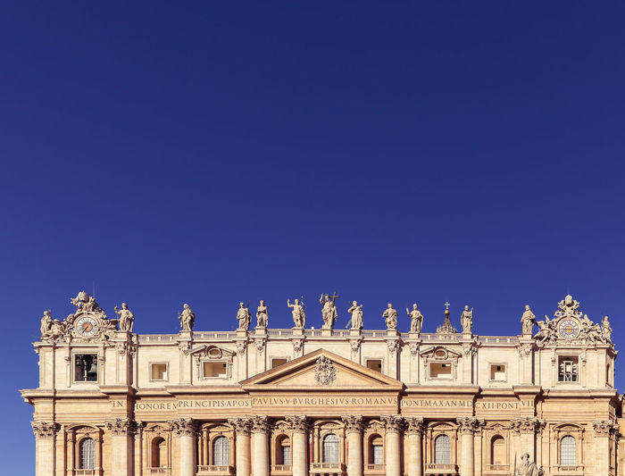 Low angle view of historical building - st. peters basilica - against blue sky, rome, vatican, italy