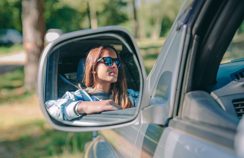 Woman wearing sunglasses reflecting on side-view mirror in forest
