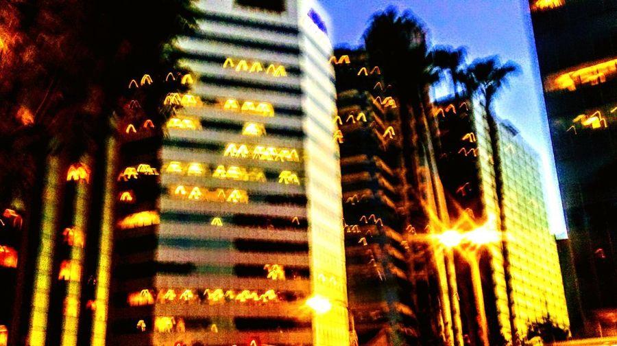 The Street Photographer - 2017 EyeEm Awards Illuminated Night Architecture Building Exterior Outdoors No People Built Structure Sky Tree Defocused CityCityscape City Light Trail Multi Colored Artofvisuals Lifestyles Skyscraper