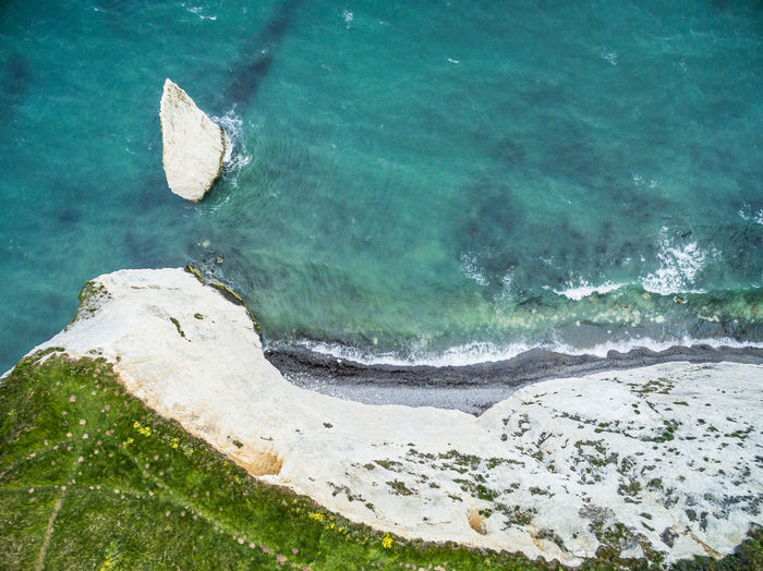 An aerial shot of the white cliffs at Old Harry Rocks in Dorset, England. Old Harry Rocks Dorset Coast Coastline Coastline Landscape Water Sea Land Rock Rock - Object No People High Angle View Outdoors Scenics - Nature Wave Nature Beauty In Nature Turquoise Colored Seaweed From Above  Rock Formation Coastal Erosion Cliff Path Coastal Britain Coastal Walk National Trust