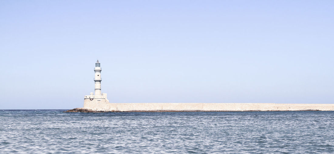 Lighthouse by sea against clear sky