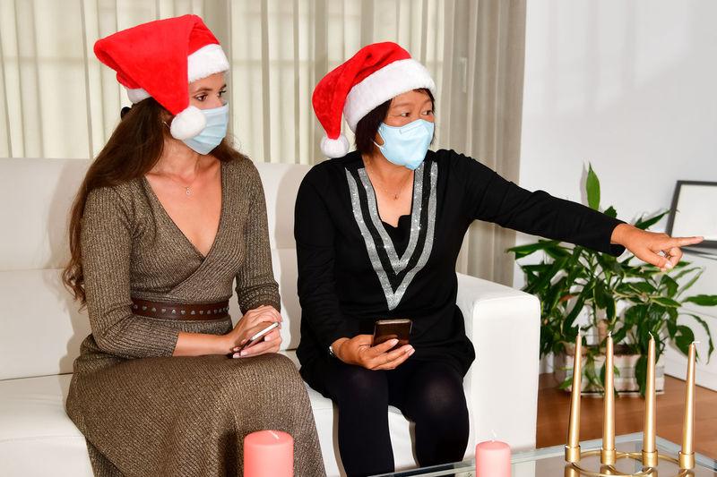 Women wearing santa hat and mask sitting at home