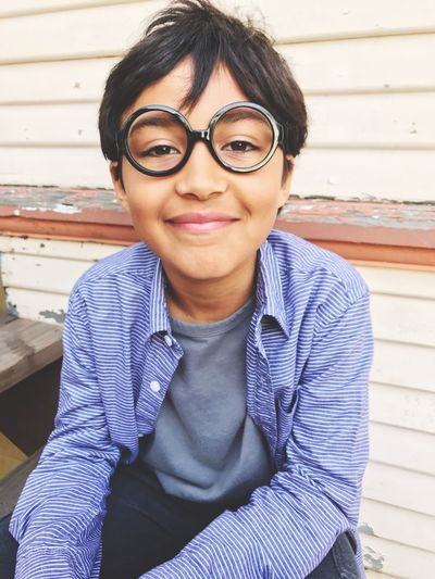 EyeEm Selects Real People One Person Black Hair Eyeglasses  Sitting Looking At Camera Portrait Front View Day Smiling Childhood Glasses Happiness Boys People Outdoors IPhoneography L. Jeffrey Moore IPhone 7 Plus EyeEm Selects
