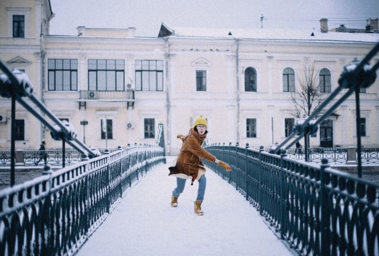 Woman walking on snow covered building