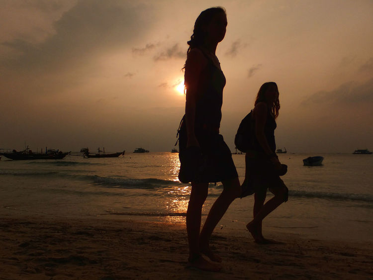 Beach Casual Clothing Childhood Full Length Horizon Over Water Leisure Activity Lifestyles Orange Color Sand Sea Shore Silhouette Sky Standing Sunset Vacations Water Spotted In Thailand Kohnangyuan