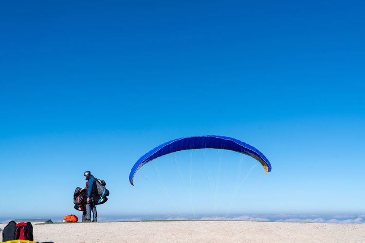 Side View Of Person Standing By Parachute Against Blue Sky During Sunny Day