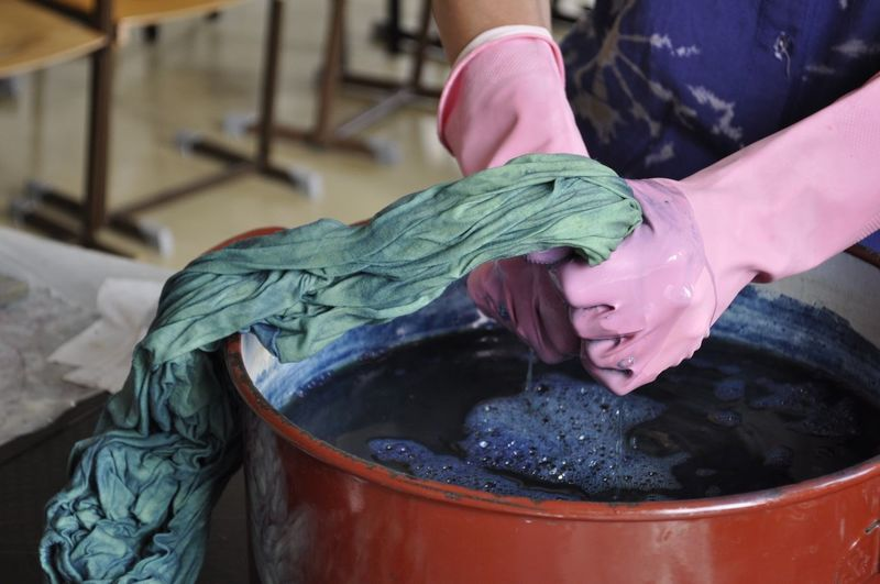 Indigo Dye Indigo Dye Cotton Cloth Indigo Dyeing Bucket Close-up Container Focus On Foreground Hand Holding Human Body Part Human Hand Indigo Indoors  Mixing Natural Dye Natural Dyeing Occupation One Person Preparation  Protective Glove Real People Small Business Women Working