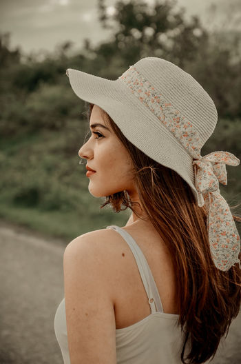 Rear view of woman wearing hat standing outdoors