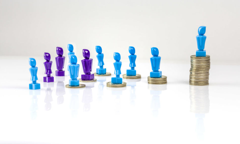 Leadership and corporate structure concept portrayed with male and femail figurines and coins. Money distribution concept. Fair pay Bar Graph Blue Business Business Finance And Industry Close-up Coins Day Female Figurines  Gender Equality Indoors  Large Group Of Objects Male No People Pile Of Coins Still Life Studio Shot Wage Gap White Background