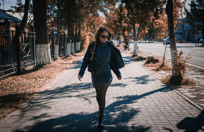 Full length portrait of woman on footpath
