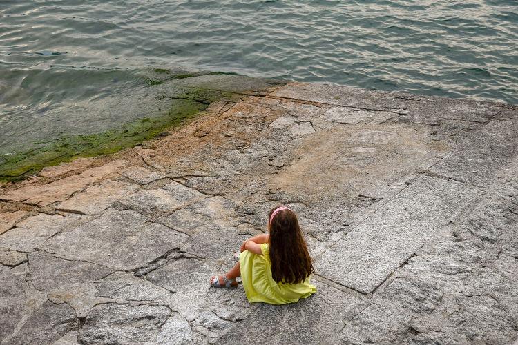 Little girl sitting on the lake shore of Lake Maggiore, Italy One Person Real People Water Sitting High Angle View Leisure Activity Lifestyles Day Nature Relaxation Rear View Casual Clothing Outdoors Hairstyle Little Girl Lake Girl At Lake Alone Serenity Calm Water Lake Maggiore Italy Tranquility Vacations Lake Shore