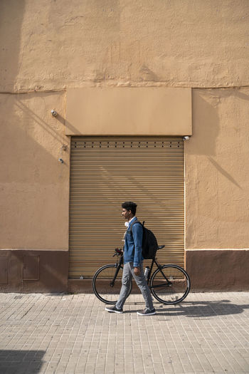 Man with bicycle on wall