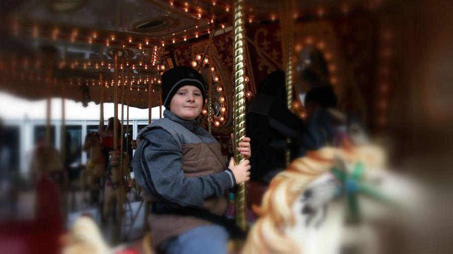 Portrait of woman sitting on illuminated carousel at amusement park