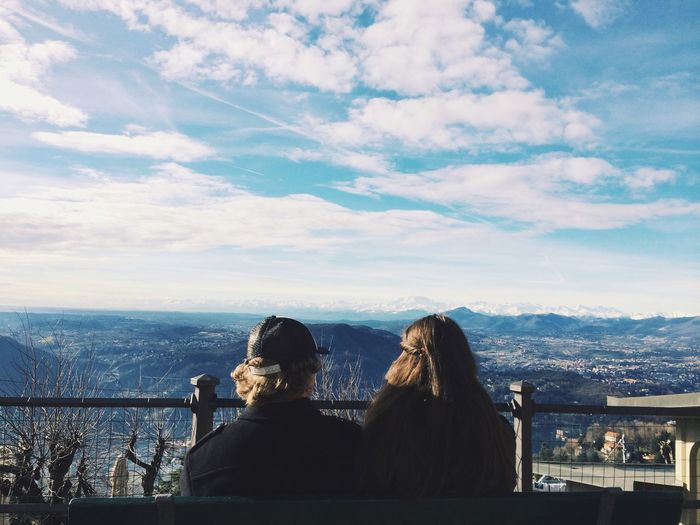 Rear View Of Couple Sitting Against Beautiful View