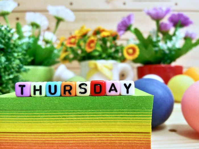 Close-up of colorful blocks with thursday text on stacked papers over table