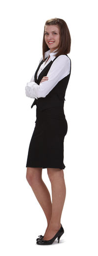 Young woman with arms crossed against a white background. White Background One Person Standing Portrait Cut Out Studio Shot Side View Young Woman Businesswoman Business Person Arms Crossed Young Adult Woman Young Cut Out On White Looking At Camera Full Length Young Adult Smiling Beauty Beautiful Woman