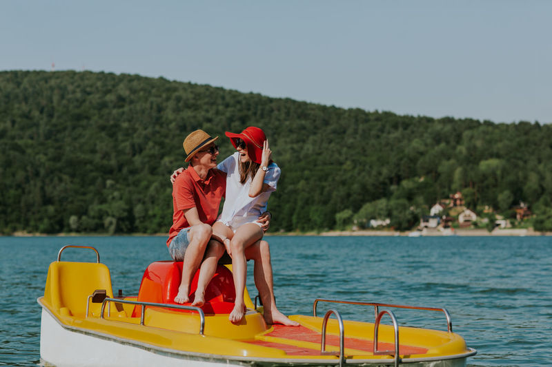 Couple in love laughing while boating in the lake. Portrait of young man and woman having fun pedal boating. Boating Couple Date Holiday Horizontal Love Man Romantic Summertime Vacations Woman Young Boat Boyfriend Caucasian Day Girlfriend Lake Outdoors Pedalo Relax Sea Summer Two People Water