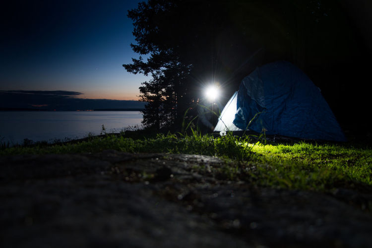 Setting up tent at night in front of water Adult Adventure Beauty In Nature Camping Camping Coastal Feature Flashlight Grass Headlamp Illuminated Leisure Activity Men Nature Night Ocean One Person Outdoors People Roadtrip Sky Tent Tree Water Woman Working Live For The Story The Great Outdoors - 2017 EyeEm Awards