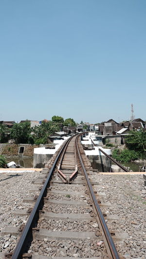 Railroad tracks against clear blue sky