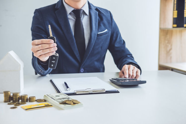 Midsection of businessman holding keys at table