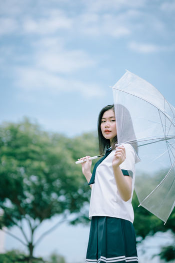 Portrait of young woman with umbrella standing against sky