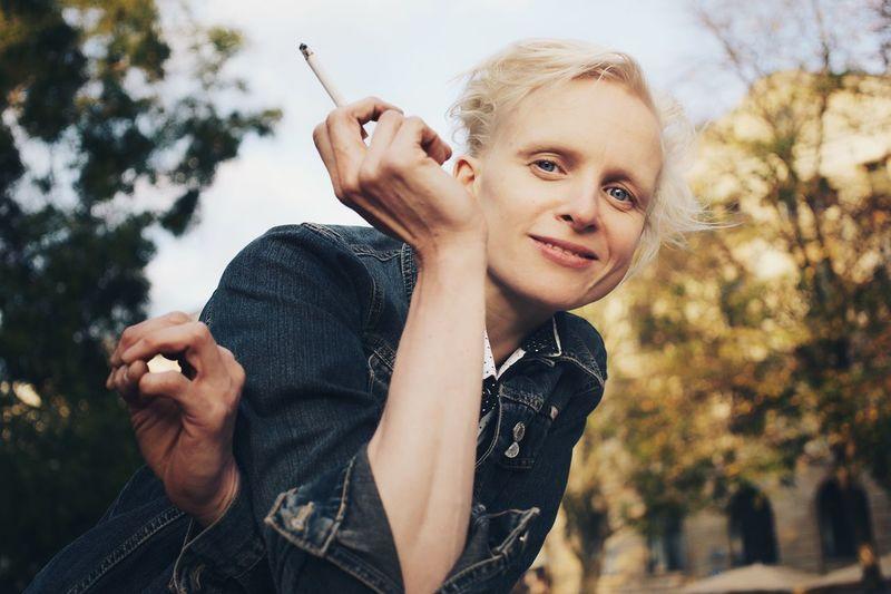 Portrait Of Woman Smoking Cigarette Against Trees