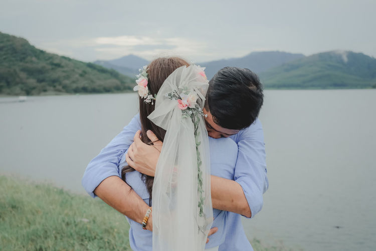 Rear view of couple standing by lake against mountains