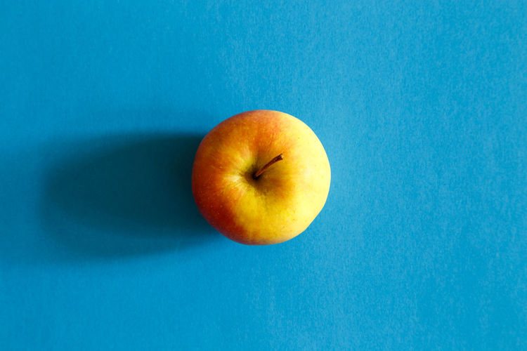 High angle view of apple against blue background