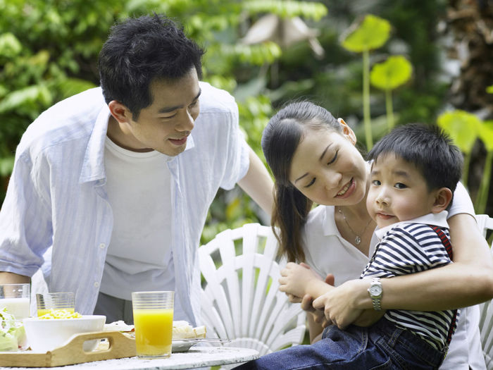 parent with single child at front yard Bonding Breakfast Casual Clothing Childhood Daughter Day Eating Family Father Food Food And Drink Happiness Healthy Eating Leisure Activity Lifestyles Mother Orange Juice  Plate Sitting Smiling Son Three People Togetherness Young Adult Young Women
