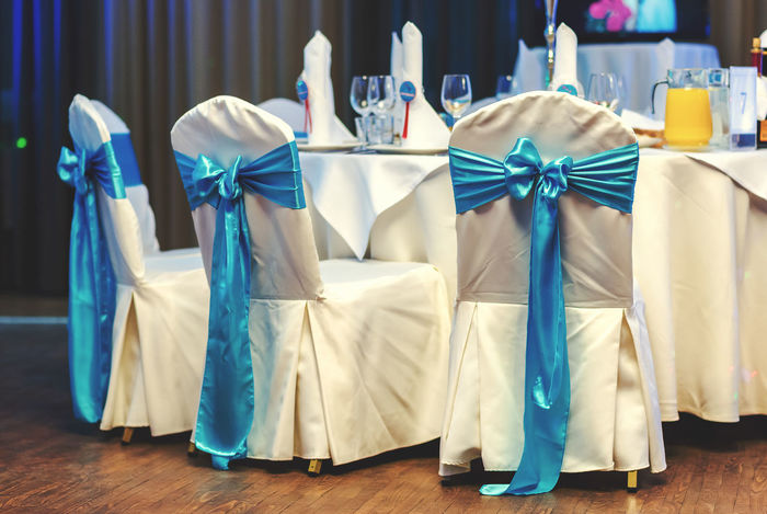White wedding chairs decorated blue bows at restaurant Banquet Beautiful Bow Decor Elegant Matrimony Ribbon Service Table Setting Wedding Wedding Reception Blue And White Catering Celebration Event Chairs Covers Decoration Linen Marriage  No People Nobody Restaurant Table Table Appointments Wedding Chairs